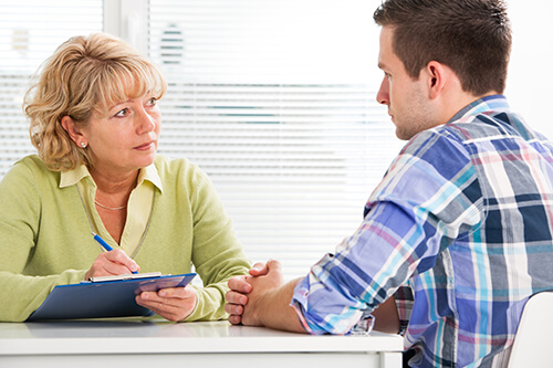 therapist talks to man about attending partial hospitalization program