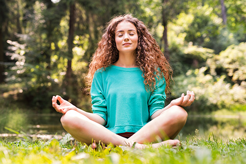 woman sitting in woods enjoys yoga therapy
