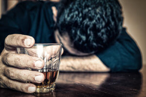 man with glass of whiskey wonders is alcohol a drug