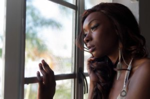 A woman somberly looks out a window thinking about her drug dependence