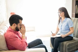 A man tries not to cry during his individual therapy session with a female therapist