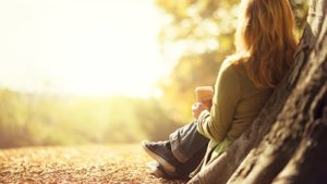 woman sitting against tree has chemical dependency problem