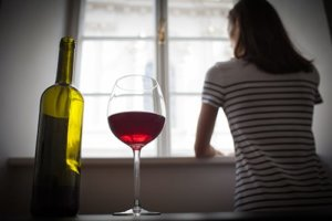 woman with bottle and glass of wine has drinking problem