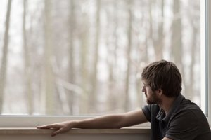man looking out window needs ptsd treatment
